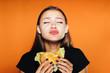 Leinwanddruck Bild - hungry girl sits on a diet, but eats an unhealthy high-calorie hamburger