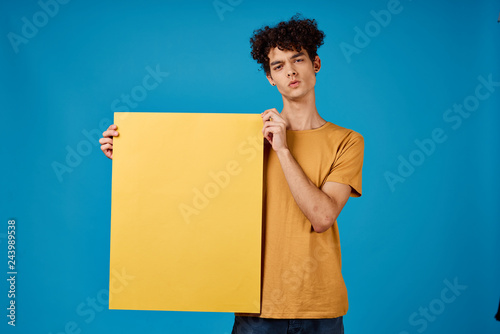 Fotografía  African man with curls holding a yellow background free space