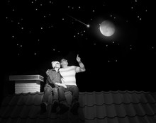 A Married Couple Is Sitting On The Roof Of A House At Night.