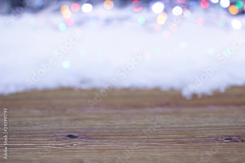 Fototapeta Empty wooden table on a background of snow and bright lights obraz na płótnie
