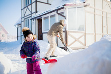 Little Girl With And Her Father Working Outdoors With A Snow Shovel.