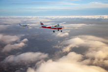 Popular Single-engine Airplane Flying Through The Clouds On A Beautiful Sunset Sky