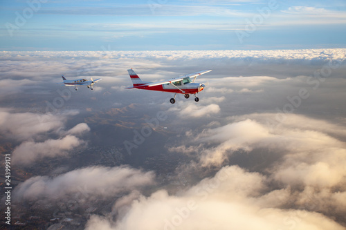 Foto Popular single-engine airplane flying through the clouds on a beautiful sunset s