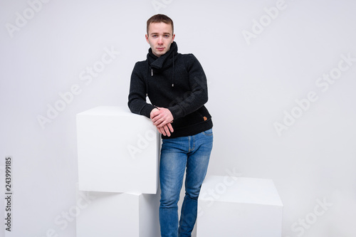 Fotografía  Concept studio portrait of a young man on a white background sitting on a cube and talking