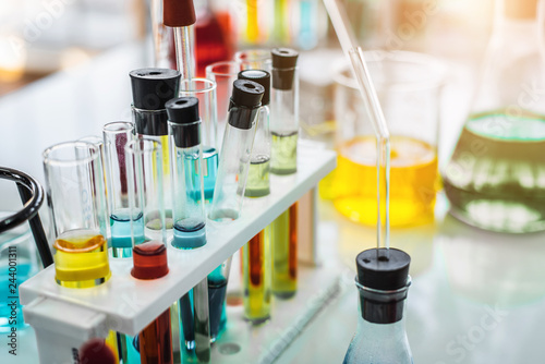 Lab glassware containing chemical liquid with laboratory background, science research and development concept