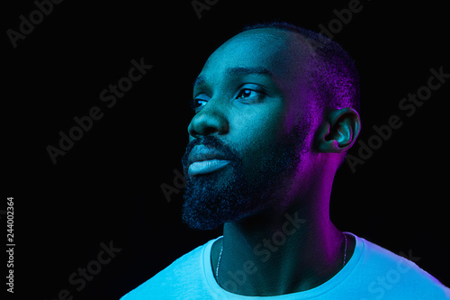 Obraz The retro wave or synth wave portrait of a young happy serious african man at studio. High Fashion male model in colorful bright neon lights posing on black background. Art design concept - fototapety do salonu