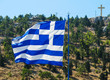 The national flag of Greece on the flagpole develops in the wind against the background of a hill with green trees and a cross on top. Greek island of Kalymnos.