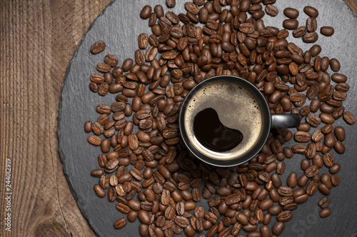 Black cup of hot coffee in coffee beans