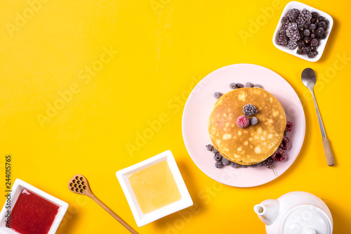 Fotografie, Obraz  A stack of pancakes on a pink plate with berries next to a plate of honey and jam with wooden spoons on a bright yellow background