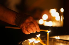 Hand Lighting Candle In A Church