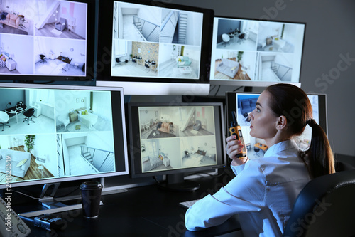 Photo Security guard monitoring modern CCTV cameras in surveillance room
