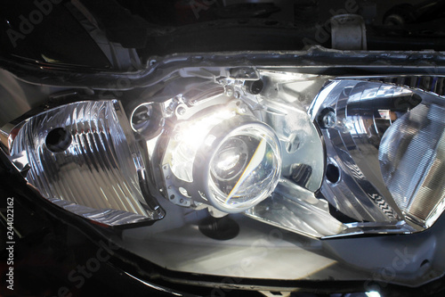 Obraz Macro view of repairing, installation and tuning headlight of modern automobile and car projector lens. Vehicle head xenon lamp in details. Concept of auto detailing, light and LED technology - fototapety do salonu