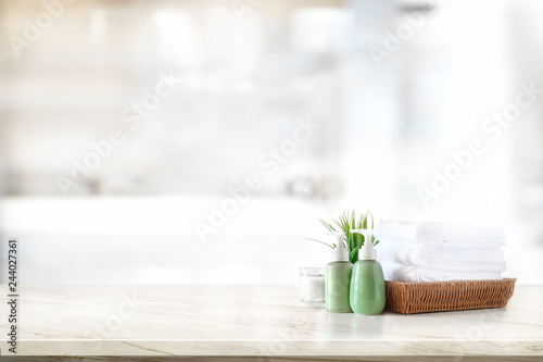 Poster Spa Ceramic shampoo, soap bottle and towels on counter over bathroom background. table top and copy space