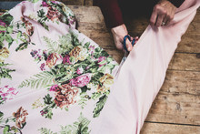 High Angle Close Up Of Woman Using Scissors To Cut Pink Fabric With Floral Pattern.