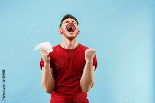 Photo Young boy with a surprised happy expression bet slip on blue studio background