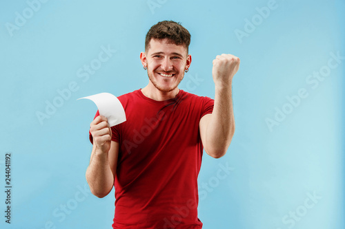 Fototapeta Young boy with a surprised happy expression bet slip on blue studio background