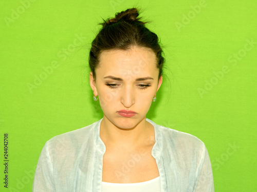 Fotografie, Obraz  Annoyed  young  girl  blowing her cheeks and looking down, feeling frustrated with something