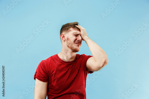 Fotomural Young boy with a surprised unhappy failure expression bet slip on blue studio background
