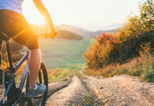 Mountain biker ride down from hill. Active and sport leisure concept