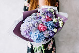 Very nice young woman holding beautiful blossoming bouquet of fresh hydrangea, roses, carnations, eustoma, flowers in pink blue and purple colours on the grey wall background