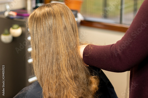 Stylist preparing brunette woman's hair for a color and highlight process