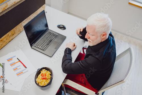 Valokuvatapetti Serious senior man talking on the phone in the office