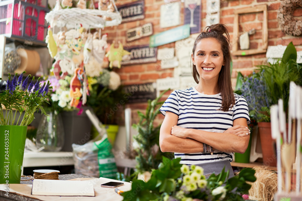 Fototapeta Picture of young florist standing in her shop and smiling at camera