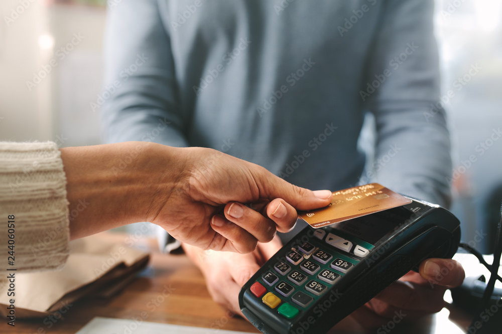 Fototapeta Pharmacist accepting credit card by contactless payment