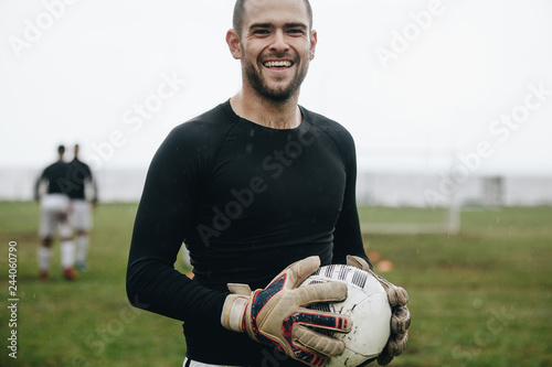 Fotografía  Close up of a smiling soccer player standing on field