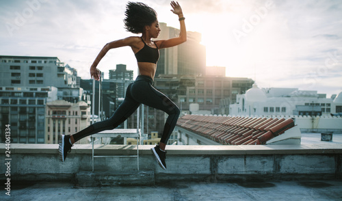Athlete woman running on rooftop Fototapet