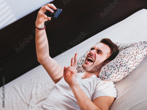 Fotografie, Obraz  Young man taking a selfie in the bed