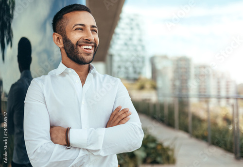 Foto  Portrait of a young confident smiling indian man with his arms crossed looking i
