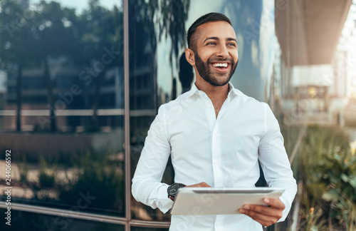 Obraz Portrait of a young confident smiling indian man holding a tablet and looking into the distance - fototapety do salonu