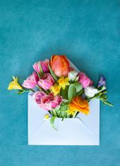 Blauer Briefumschlag mit frischen Blumen