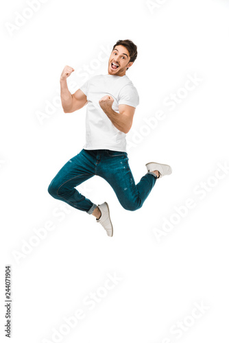excited young man jumping and smiling at camera isolated on white Fototapeta