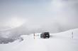Van driving along snowcapped mountain road