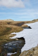 Snow Drift And Boggy Stream In Marsh Moorland