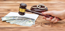 Woman's Hand Holding Gavel Over Table With Money In Envelope And Handcuffs.