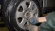 Closeup view of a mechanic spinning a car wheel