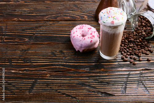 Fotografia  A donut with pink icing and chocolate powder and a cappuccino glass with high foam and decoration
