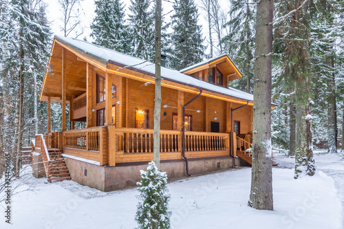 Snow-covered beautiful wooden house in the forest at dusk Wallpaper Mural
