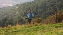 Young Man In The Mountains Looks For Buried And Forgotten Treasures With His Metal Detector.