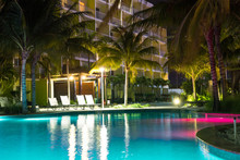 Beautiful Resort Hotel Pool At Night With Lights And Palm Trees In Tropical Location