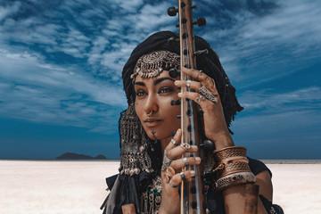 Beautiful young stylish tribal woman in oriental costume playing sitar outdoo...