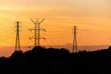 Silhoutte Of Los Angeles Skyline Seen Through Power Lines During A Golden Sunset.