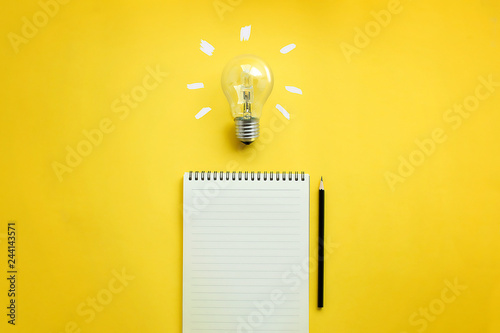 Photo  Flat lay of light bulb and empty memo pad and pencil on yellow background with texts