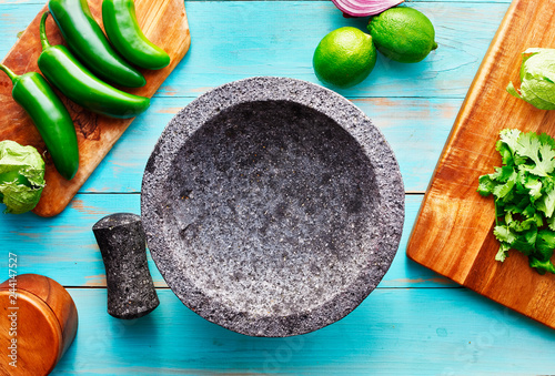 empty molcajete on table with ingredients ready to prep