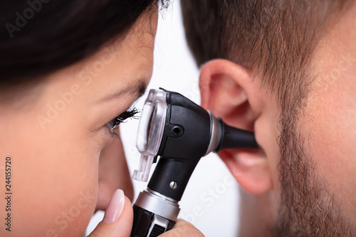 Doctor Examining Male Patient's Ear Wallpaper Mural