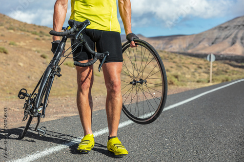 Bike repair cyclist man on side of road repair road bicycle problem with wheel. Cycling outdoor athlete biker biking with cycle.