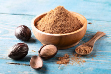 Whole Inshell Nut And Nutmeg Powder In A Wooden Bowl And Spoon On Old Blue Rustic Background.